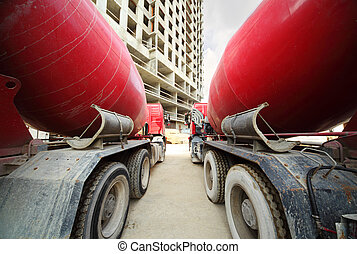 Between two concrete mixer standing near unfinished tall...