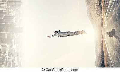 Between two worlds - Young businessman making jump between...