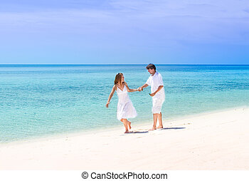 Beuatiful young couple running on a tropical beach