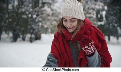 Beutiful Young Girl in the snowy forest makes a selfie. Slow motion. Portrait of stylish young beautiful girl in a winter park