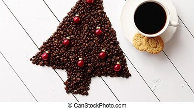 Beverage and cookies near Christmas tree from coffee beans -...