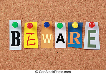 The word Beware in cut out magazine letters pinned to a corkboard.