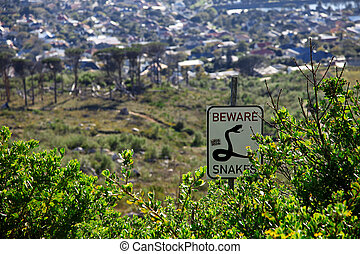 Beware snakes sign post in the bushes of Capetown, South Africa