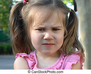 Little girl frowns in bewilderment and confusion. Closeup shows head and pigtails.