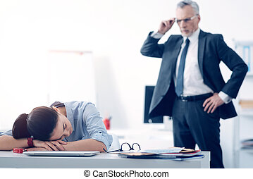 Bewildered chief looking at his employee sleeping at work