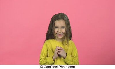 Bewitching child with smile is clapping her hands on pink...