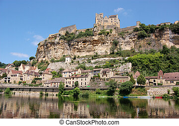 The Chateau de Beynac towers over the town of Beynac which clings to the rocks in a bend of the Dordogne river, France