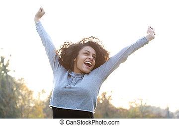 beztroski, młoda kobieta, uśmiechanie się, z, herb podniesiony
