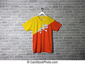 Bhutan flag on shirt and hanging on the wall with brick pattern wallpaper.