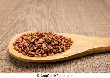 Bhutanese Red Rice seed. Grains in wooden spoon. Rustic.