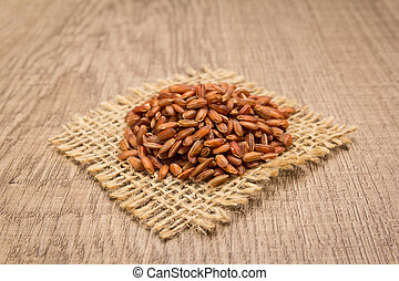 Bhutanese Red Rice seed. Grains on square cutout of jute. Wooden table. Selective focus.