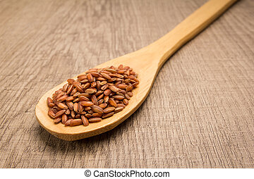 Bhutanese Red Rice seed. Spoon and grains over wooden table.