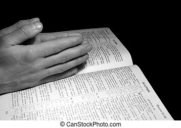 bible - A mans hands clasped in prayer over a Bible