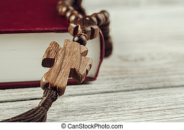 Bible and a crucifix on an old wooden table. Religion concept.