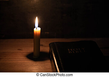 Bible and candle on a old oak wooden table.
