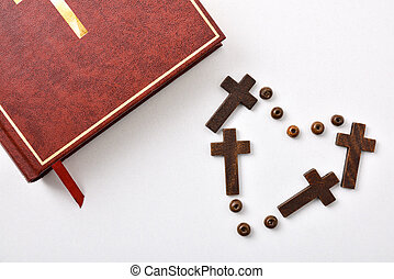 Bible and heart made with crosses and beads on table
