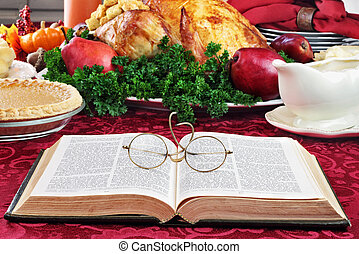 Bible and Holiday Dinner - Open Bible with glasses lying on ...