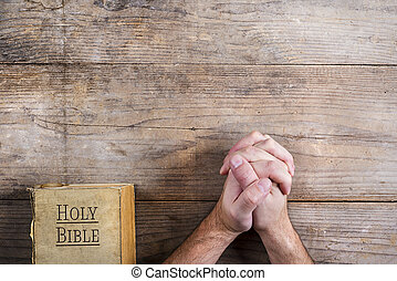 Bible and praying hands - Hands of praying young man and...