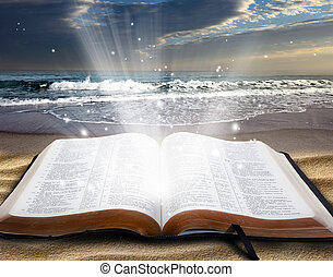 Open bible on the beach at sunset