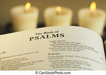 A closeup image of the first page of The Book Of Psalms with burning candles in the back ground
