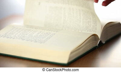 Bible Book scrolling by woman hand