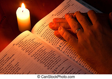 Bible by candle light with hands resting on it