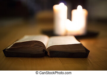 Bible laid on wooden floor, burning candles in the...