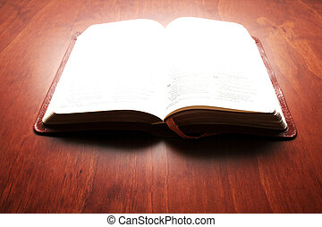 Bible Lit Up - Bible with bright light on the open pages as...