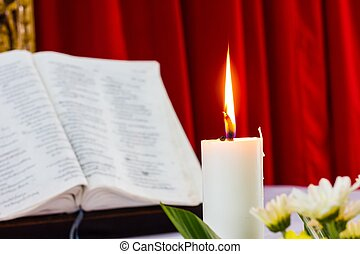 bible open on a table with candle and red curtain as...