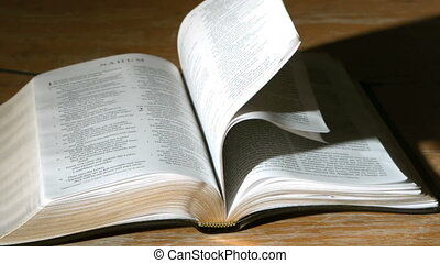 Bible pages turning in the wind in slow motion