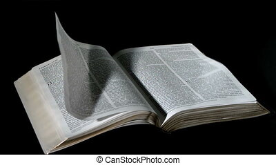 Bible pages turning in the wind on