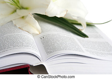 Bible and easter lilies on a white background