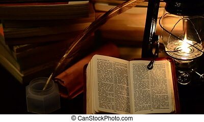 Bible study - A bible surrounded by books in a lamp light
