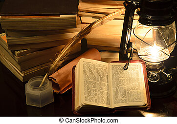 bible study - a bible surrunded by books in a lamp light