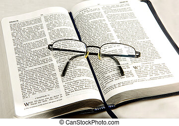 Bible whit eye glasses. - A pair of reading glasses on top ...