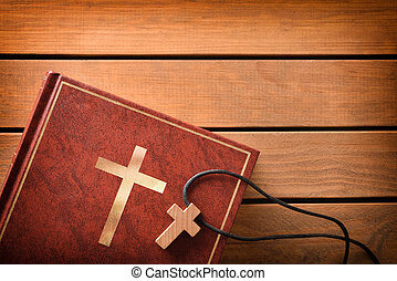 Bible with cross shaped pendant on wooden slatted table