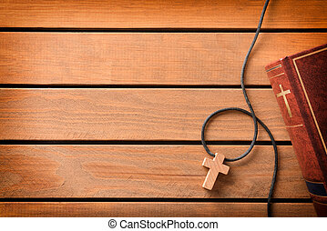 Bible with cross shaped pendant on wooden slatted table top