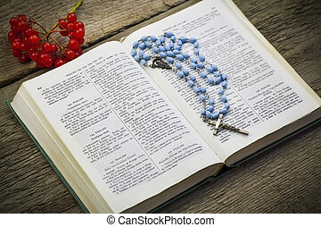 Bible with rosary on old boards