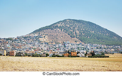 Mentioned in the Bible Mount Tabor and the Arab city at its foot.
