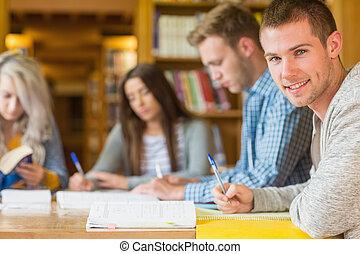 biblioteca, estudante, escrivaninha, sorrindo, macho, amigos