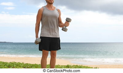 Bicep Curl exercise - fitness man exercising biceps with dumbbells arm curls on beach. Fit sport fitness model showing correct technique in classic weight lifting workout exercise. REAL TIME.