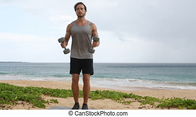 Bicep Curls exercise - fitness man exercising biceps with dumbbells on beach. Two-arm biceps curls workout by fit sport fitness model. SLOW MOTION.