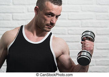 Biceps Exercise With Dumbbells On White Bricks Background
