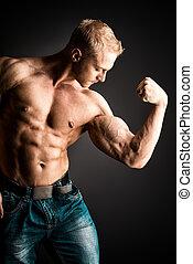 biceps - Muscular bodybuilder man posing over dark ...