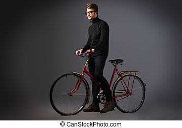 Stylish handsome young man in black clothes and spectacles standing with the old bicycle.