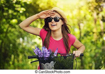 bicicleta, mujer feliz, algo, mirar