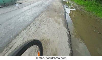 Bicicling on old city asphalt roads after rain.