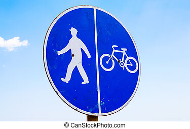 Bicycle and pedestrian lane sign against the blue sky
