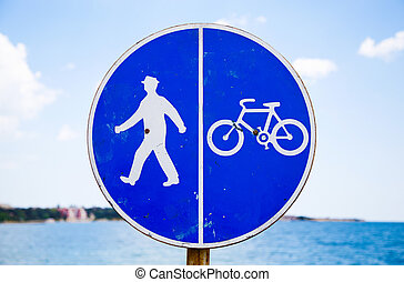 Bicycle and pedestrian lane sign against the sea