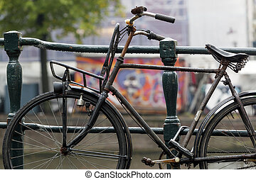 Bicycle attached to bridge railing in Amsterdam